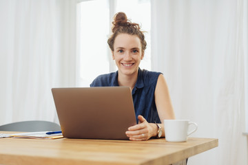 Happy young woman sitting studying at home