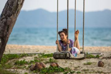 Young mixed race woman lies on the swings on Sea beach.