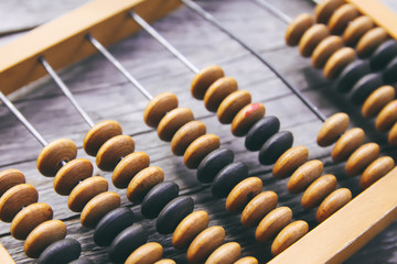 Vintage wooden abacus on old board surface.