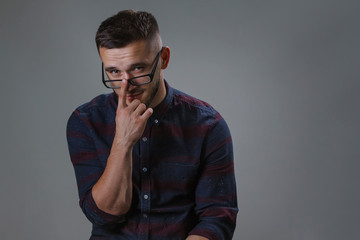 A close-up portrait of a man who straightens his glasses with his hands. Attractive male wearing checkered shirt and strong black plastic glasess for low eyesight while stands on a gray background