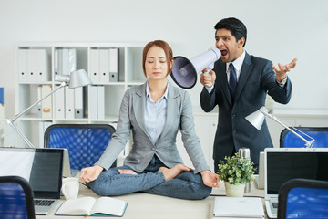 Businessman screaming in megaphone and trying to awake his colleague while she meditating in work time