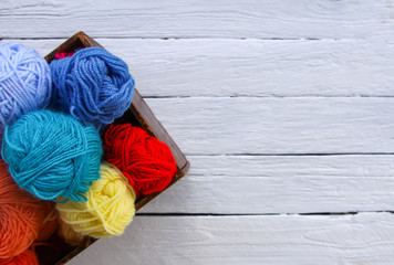 Colorful yarn balls in wooden box on white wood boards background.