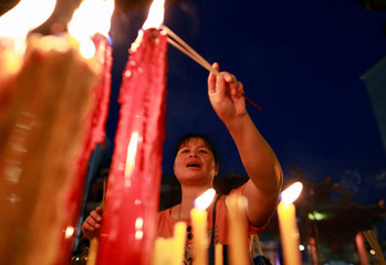 A woman lights sticks of incense during a vegetable festival in Chinatown at Bangkok