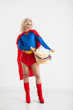 Full-length portrait of beautiful Caucasian female in superwoman costume standing on white background with basket of dirty laundry and smiling at camera