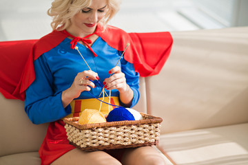 Young beautiful blond Caucasian woman wearing superwoman costume knitting while sitting on couch with basket of yarn