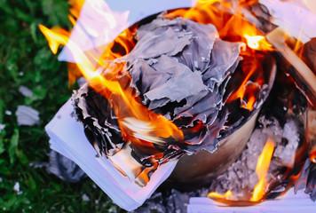 Paper burning on green summer grass outdoors.
