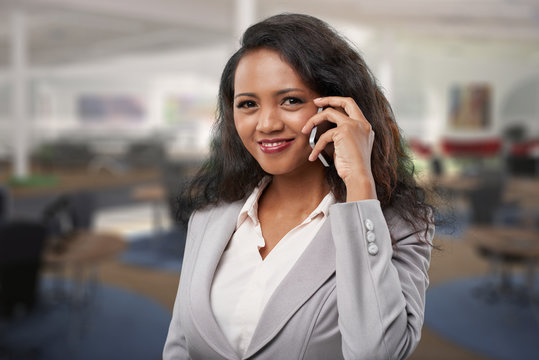 Cheerful confident young business lady with curly hair standing in open space office and looking at camera while communicating on mobile phone