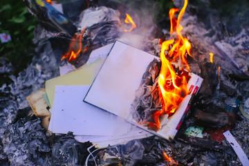 Notepad burning on green summer grass outdoors.