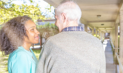 African doctor reassuring elderly patient in hospital garden