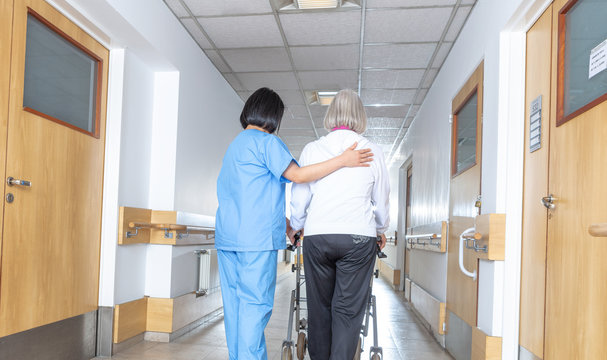Asian doctor helping elder woman with walker in hospital hallway