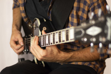 man playing on electric guitar close-up, music concept