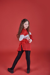 Young beautiful cute girl dancing on red background, modern slim hip-hop style teenage girl jumping