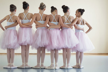 Group of ballerinas posing together with back to camera