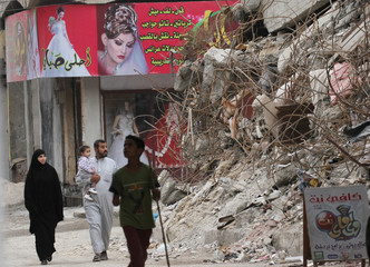 People walk past the rubble of damaged buildings in Raqqa
