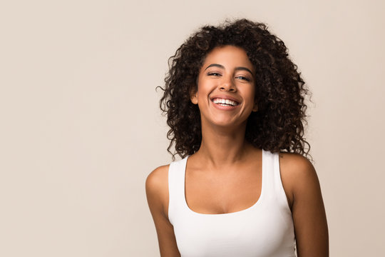 Portrait of laughing young woman against light background