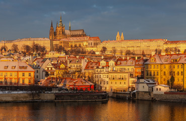 Beautiful Prague's cityscape during early winter sunrise, with some of its famous landmarks, including the Prague Castle and St. Vitus Cathedral, being illuminated by the morning sunlight