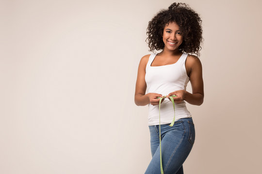 Happy african-american woman measuring waist with tape