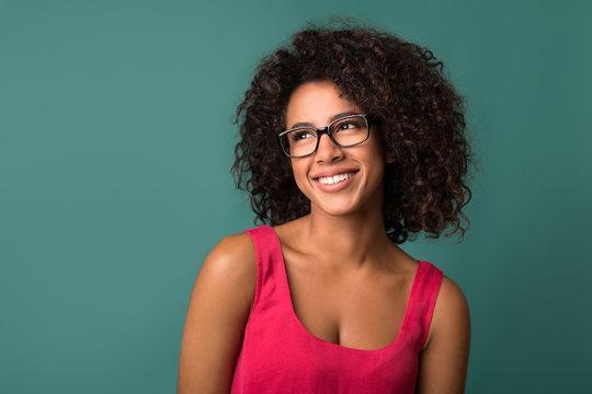 Beautiful african-american girl in eyeglasses looking away against wall