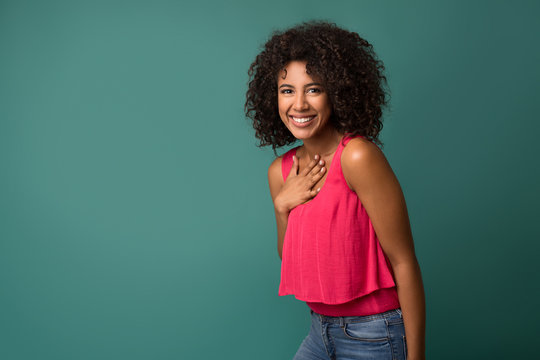 Cheerful african-american woman holding hand on chest