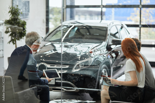 Portrait Of Two Car Buyers Reading Sale Contract And Signing A Car