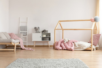 Bright kid bedroom interior with grey sofa, cupboard with boxes and toy and house-shaped bed with powder pink blanket in real photo