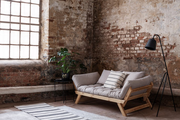 Grey wooden couch between plant and lamp in loft interior with red brick wall and window. Real photo