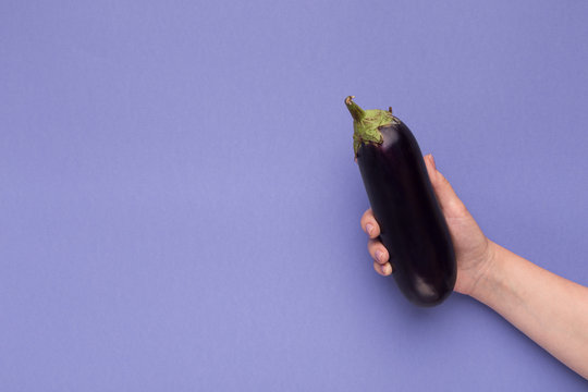 Female hand holding fresh eggplant on purple background