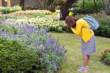 Woman taking photo in flowers garden.