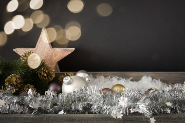 Christmas decoration with glass balls wooden star and bokeh lights background