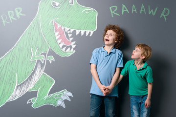 Frightened boys and enormous dinosaur