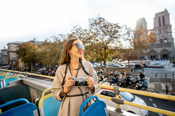 Young woman enjoying a beautiful view on the Notre-Dame cathedral during a bus tour in Paris, France