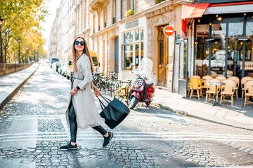 Street view with traditional french cafe and woman walking during the morning in Paris Wall mural