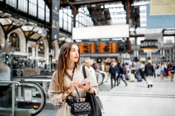 Young woman waiting for the train standing indoors at the railway station in Paris Wall mural