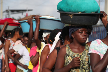 Haitian women are waiting in line to cross the border and trade their products, in Dajabon