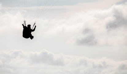 Paragliding pilot silhouette in the fluffy clouds sky.