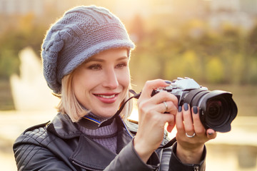 stylish blonde woman photographer takes pictures of autumn forest at sunset