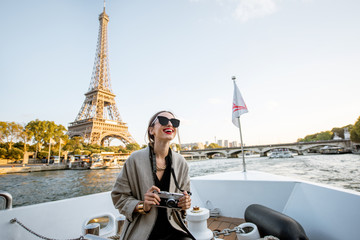 Young woman enjoying beautiful landscape view on the riverside with Eiffel tower from the boat during the sunset in Paris