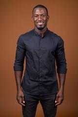 Portrait of handsome African businessman against brown background