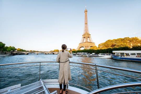 Young woman enjoying beautiful landscape view on the riverside with Eiffel tower from the boat during the sunset in Paris. Wide view with copy space