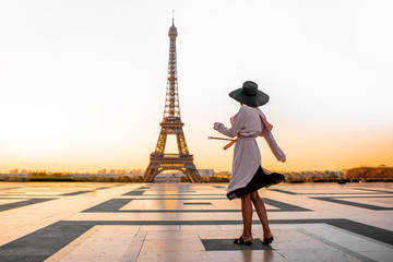 Woman dressed in coat and hat walking on the famous square with great view on the Eiffel tower early in the morning in Paris Fotomurales