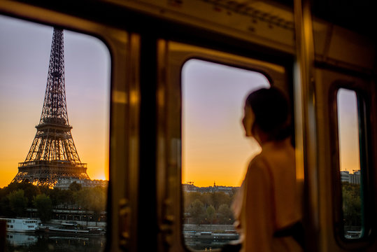 Young woman enjoying view on the Eiffel tower from the subway train during the sunrise in Paris. Image focused on the background