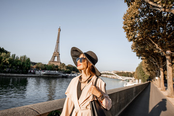 Young woman tourist walking on the riverside with beautiful landscape view on the Eiffel tower during the morning light in Paris