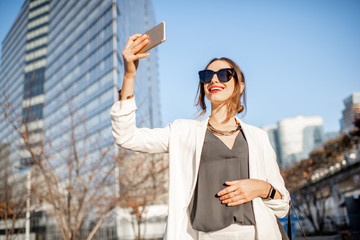 Portrait of a young stylish businesswoman standing with phone at the business center outdoors