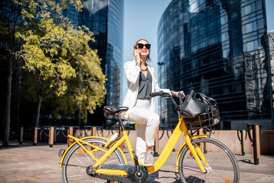 Portrait of a stylish business woman in white suit standing with bicycle at the financial district with modern buildings on the background