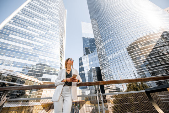 Portrait of a young business woman outdoors with high skyscrapers on the background