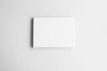 Fototapeta White canvas on gray wall. Mock-up poster frame in interior.
