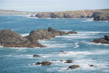 Views of the North Cornwall coast near Mawgan Porth with surf, clifffs and spray on a clear day