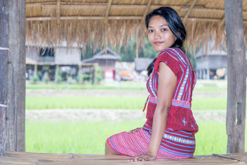 Asian woman in traditional costume for Karen resting beside green rice field