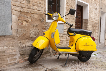 Viejo scooter amarillo aparcado en calle de pueblo