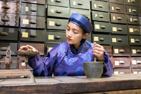 Asian pharmacist working at oriental pharmacy from the 19th century. Woman in traditional costume eastern druggist in the ancient drug store.